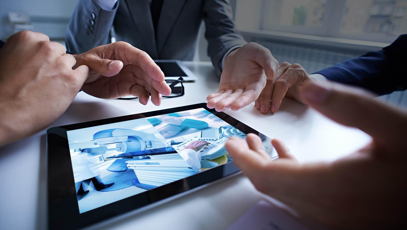 タブレットに映る医療機器、医薬品をみながら協議する認証・承認取得のプロフェッショナル達